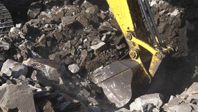Excavator digging ore close-up. Bucket excavator rakes rock. Open pit mining.