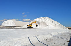 Excavator Digging Salt - JCB Excavating Mountain. A Cat type of excavator being used to move salt stock images