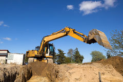 Excavator digging sewer trenche Stock Photos