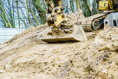 Excavator digging on site in forest environment. Yellow excavator dig digging trench on construction site in forest among trees. Devastation destruction of Royalty Free Stock Photos