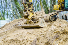 Excavator digging on site in forest environment. Yellow excavator dig digging trench on construction site in forest among trees. Devastation destruction of Royalty Free Stock Photo