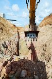 Excavator digging a trench for the pipeline. Bucket closeup royalty free stock image