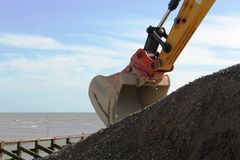 Excavator digging up shingle on the beach. A close up of a yellow excavator digging up shingle on the beach Stock Image