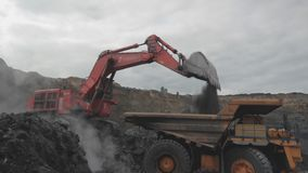 An excavator bucket digs coal. An excavator digs coal and pours it into a large yellow dump truck. Open pit coal mining stock video footage