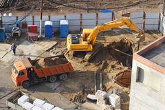 Excavator digs hole at construction site. Royalty Free Stock Photo