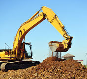 Excavator And Dirt. A large yellow excavator moving a large pile of dirt with debris falling from the bucket Stock Photo
