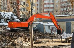 Excavator dismantles dilapidated housing. The excavator dismantles the remains of dilapidated housing, whose inhabitants were moved to new homes in the Stock Photo