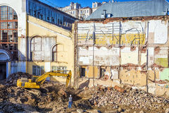 Excavator on the dismantling of the old stone house Stock Image