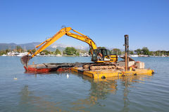 Excavator dredging on floating platform Stock Photos