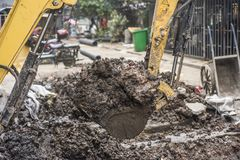 An excavator dug a bucket of dirt. At the construction site of the city, a small excavator dug a bucket of dirt and was photographed in Qinhuai District, Nanjing stock photography