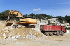 Excavator and dump truck. Excavator loading sand into dump truck Stock Image