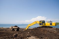 Excavator.dump truck.sea Stock Photography