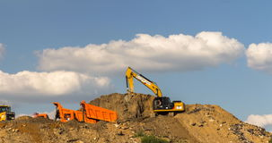 Excavator and dump truck skill work on construction of new highway. A stock video footage