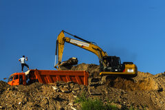 Excavator and dump truck skill work on construction of new highway. A. Moscow; Russia, August -eleventh-Two thousand sixteen year;  excavator and dump truck Royalty Free Stock Photography