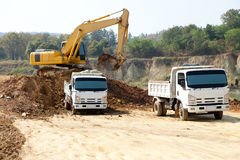 Excavator and dump truck tipper in construction site Royalty Free Stock Image