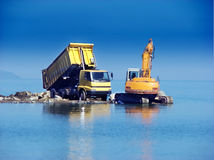 Excavator and dumper. Working in the sea Royalty Free Stock Image