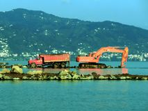 Excavator and Dumper. Working in the sea Stock Photos