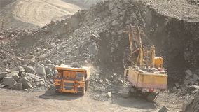 Excavator and dumper in the quarry, excavator loads the raw materials in the dumper, work in the iron ore quarry. Excavator and dumper in a quarry, a yellow stock footage