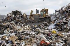 Excavator At Dumping Ground. Excavator moving garbage at dumping ground stock photo