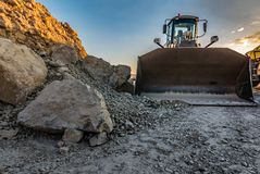 Excavator at dusk in a stone quarry stock photo