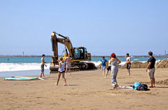 Excavator and Eight People on Beach in Durban Stock Photography