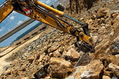 Excavator engineer moving sand and rocks with heavy duty scoop Stock Photo