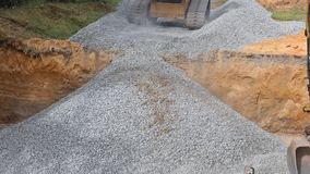 Excavator extracting backfill of foundation stone