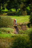Excavator in Field. An excavator digs a draining ditch in a field stock photo