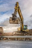 Excavator filling a truck with earth for the construction of a slope for the construction of a road royalty free stock image
