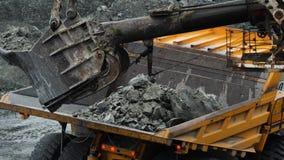 Excavator fills dump truck. Bucket excavator closeup loads stones into body of dump truck on mining or construction of stock footage