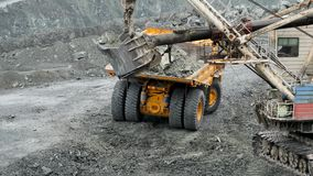 Excavator fills of truck. Excavator digs hole and transfers land to body of dump truck on construction site or mining.  stock video footage