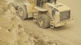 Excavator with a flat tire going backwards stock footage