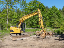 Excavator in the forest preparing construction of  the hiking tr Stock Photography