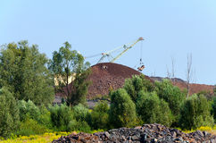 The excavator on formation of quartzite dump Stock Photos
