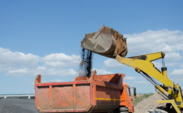 Excavator on gravel pile loading a truck Royalty Free Stock Photos