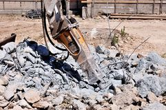Excavator with hammer demolishes Royalty Free Stock Photos