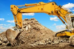 Excavator and heap of dirt in front of blue sky Royalty Free Stock Photos