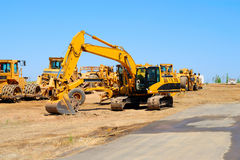 Excavator And Heavy Equipment. Heavy construction equipment sits idle lined up along a new asphalt road Royalty Free Stock Photography