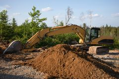Excavator Heavy Equipment Machine in the Summer on a Job Site stock photo
