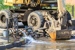 Excavator helps to eliminate the problem of breaking a pipe in the street on a hot summer day.  royalty free stock photos