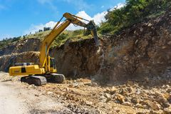 Hydraulic hammer destroys rock in road construction. Excavator with hydraulic breaker destroys rock in road construction royalty free stock photos