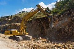 Hydraulic hammer destroys rock in road construction. Excavator with hydraulic breaker destroys rock in road construction royalty free stock photography