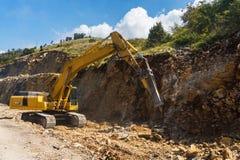Hydraulic hammer destroys rock in road construction. Excavator with hydraulic breaker destroys rock in road construction stock image