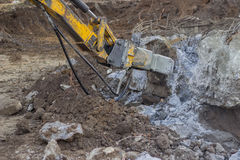 Excavator with hydraulic hammer breaking concrete 2 Royalty Free Stock Image