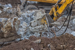 Excavator with hydraulic hammer breaking concrete 3. Excavator with hydraulic hammer breaking concrete on a construction site Royalty Free Stock Photos