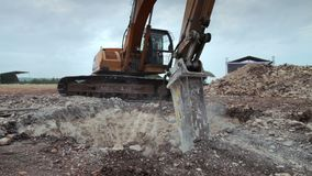 Excavator with hydraulic hammer drill at work breaking down earth for construction stock footage
