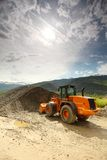 Excavator In Alps Stock Photo