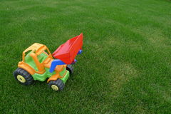 Excavator on a lawn. Excavator toy on a lawn Royalty Free Stock Images