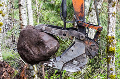 Excavator lifts a large rock Stock Photography