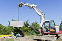 Excavator llifting concrete ring Royalty Free Stock Photography
